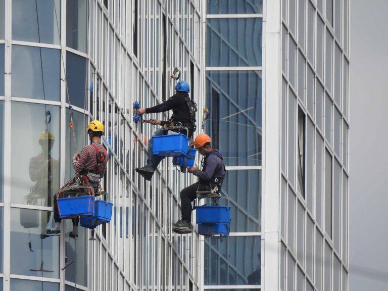 Мытье окон офисов промышленными альпинистами