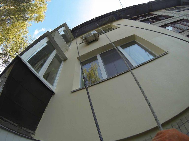 Утепление фасада квартиры на высоте пенопластом.