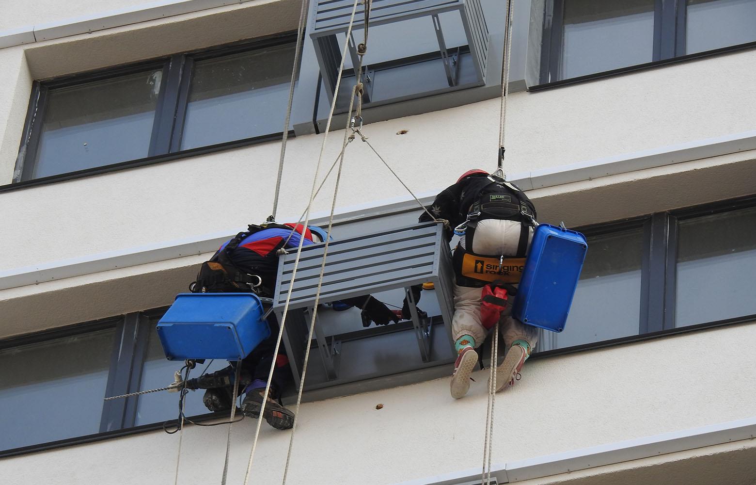 Установка корзины для кондиционера альпинистами.